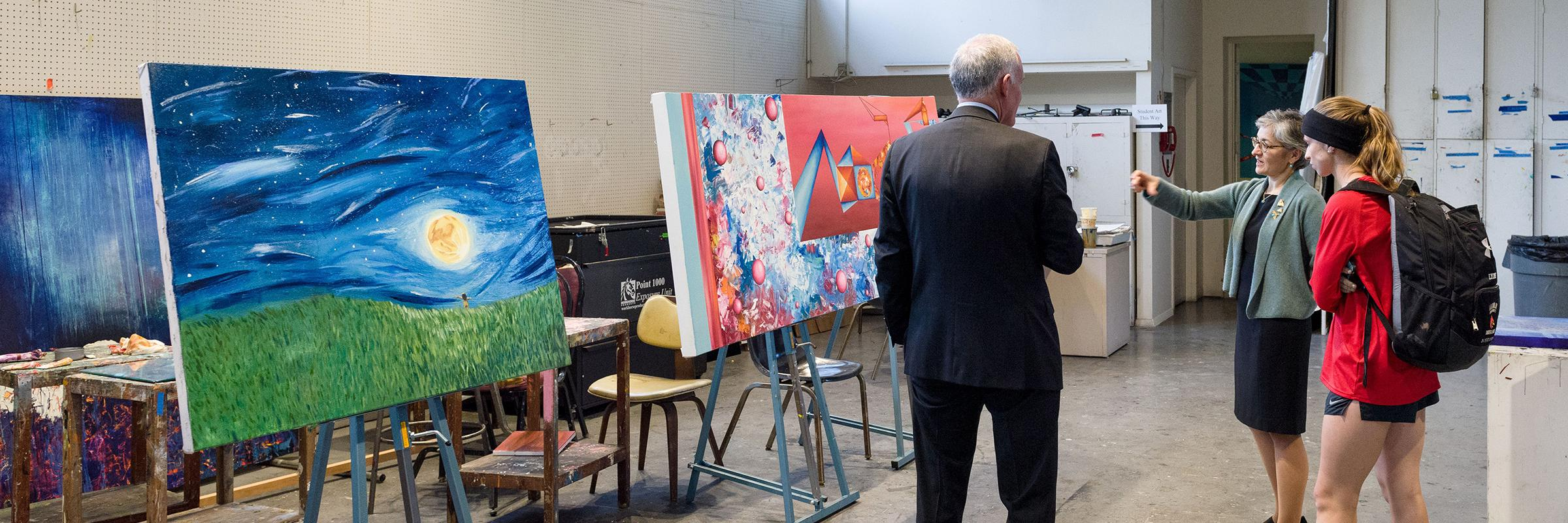 Looking at student art in Salve Regina Gallery