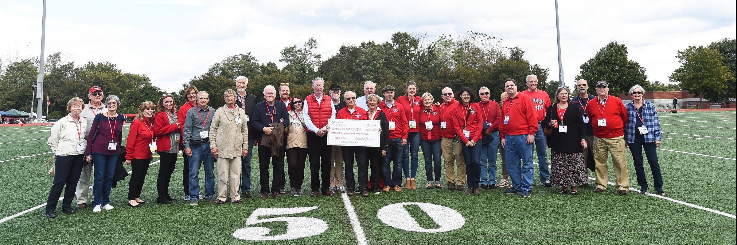 Reunion alumni holding a large check on a football field