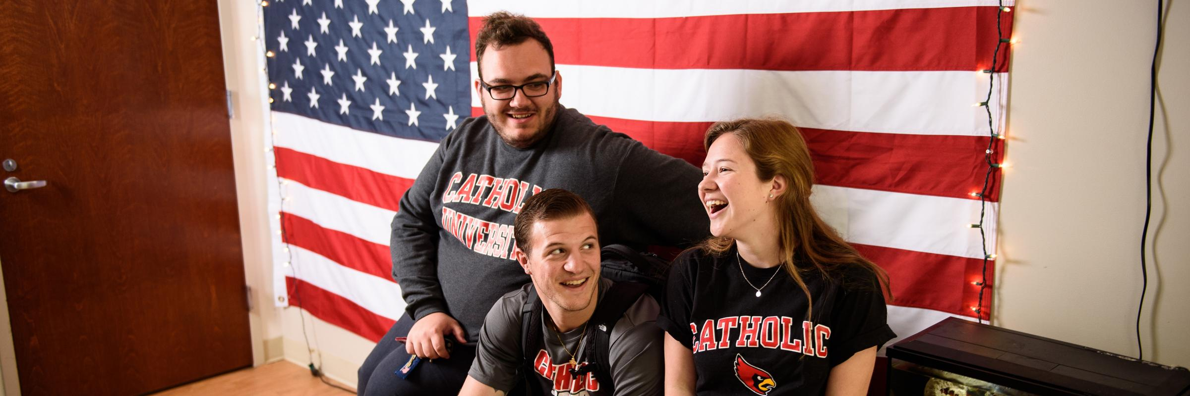 Students smiling in a dorm with a U.S. flag behind them