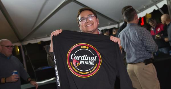 Student selling Cardinal Weekend merchandise