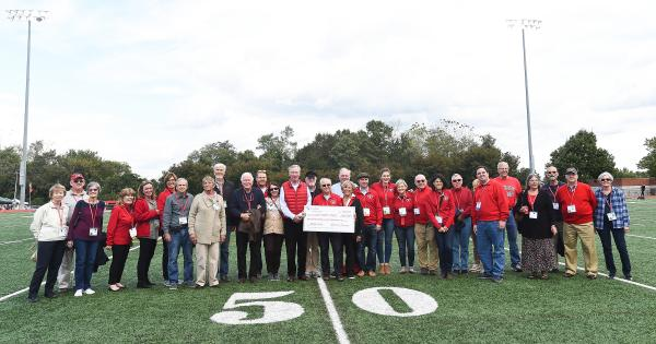 Reunion alumni holding a large check on the football field